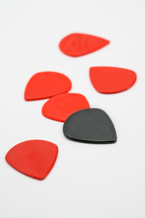 Red and black plastic guitar picks isolated on white background with shallow depth of field
