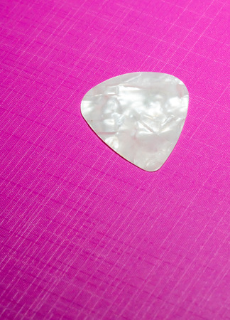 Whtie plastic guitar plectrum isolated on pick background. Guitar Pick
