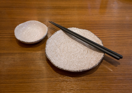 A set of ceramic plate with black chopstick placing on top and sauce bowl on wooden brown table in Japanese style.