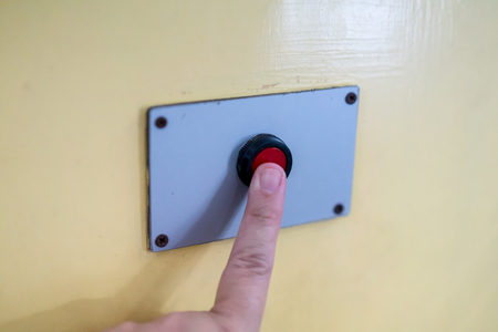 A finger reaches for pressing the red button on yellow background