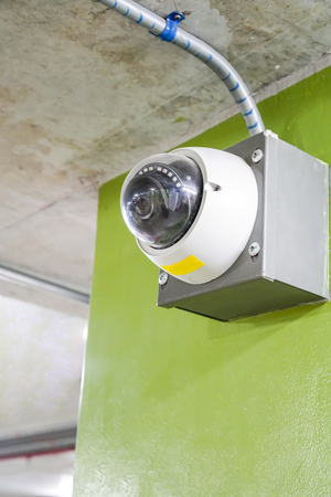 CCTV security camera installed near ceiling building. Dome outdoor cam for parking area.