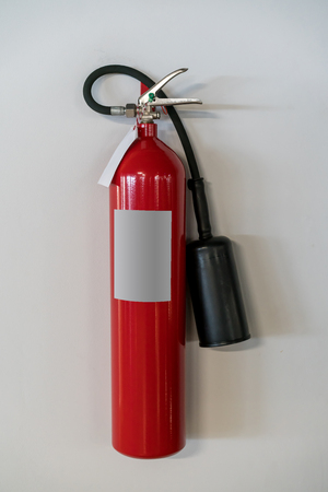 Red fire extinguisher hanging against white wall background