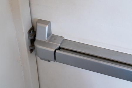 Scrocco chiuso e maniglia della porta di uscita di emergenza. Barra di spinta e binario per uscita antipanico. Archivio Fotografico