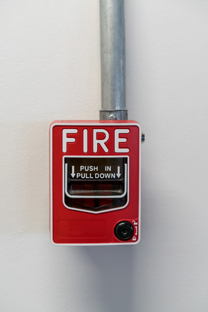 push in pull down switch fire installed against white wall