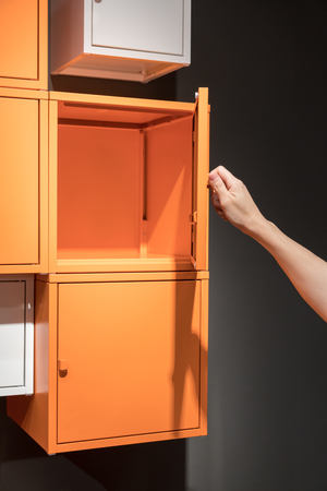 Hand open the orange metal cabinets hanging on black wall for decoration Stock Photo