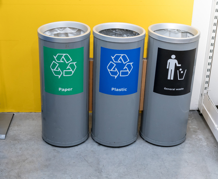 Different color trash cans in row for waste management. Perspective disposal view for saving environmental concept. Imagens