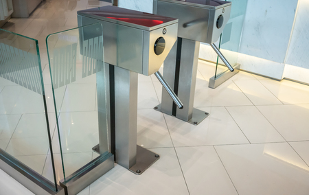 Automatic silver metallic security turnstile station against beige tile floor. Stockfoto