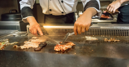 Hand of Chef cooking chicken steak on hot pan in front of customers. Japanese Tepanyaki Steak