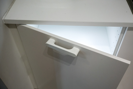 Small white cabinet with LED lighting inside. Automatic illuminated system door when opened. Stock Photo