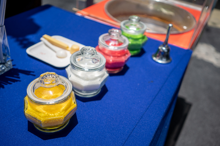 Many colored granulated sugar in glass jar in row on blue table for making cotton candy in luxury restaurant.