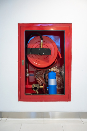 Fire Hose Cabinet on orange bricks floor against white concrete wall. Stock Photo
