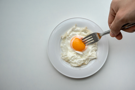 Hand holding fork to prick the egg yolk of beautiful fried egg in white plate isolated on white background.