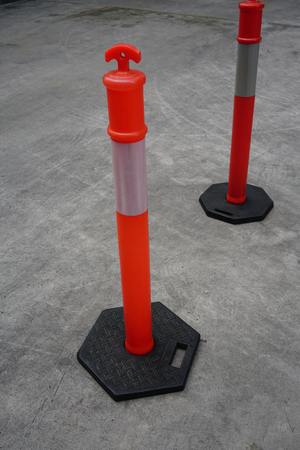 Red plastic poles with white strip lines for traffic on concrete road