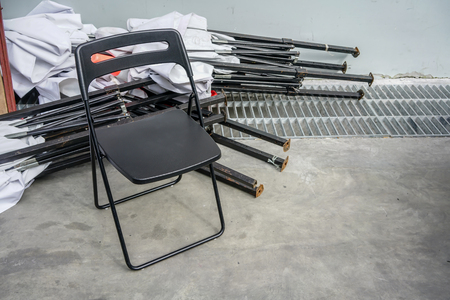 Single black metal folding chair for foreman resting at outdoor site.