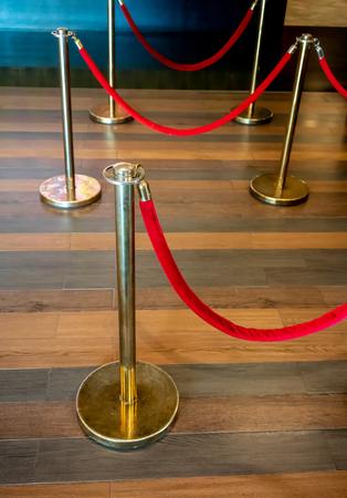 Gold metal poles with red fabric rope barriers. Closed up for detail at the mall. Reklamní fotografie
