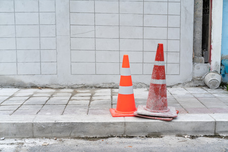 Two orange traffic cones on footpath concrete and road. Stock Photo