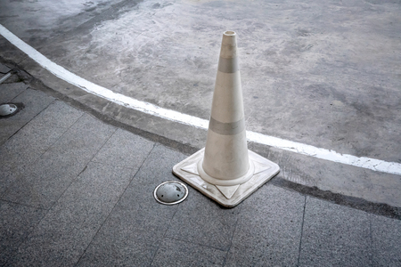 White traffic cone on concrete road standing by walkway or footpath