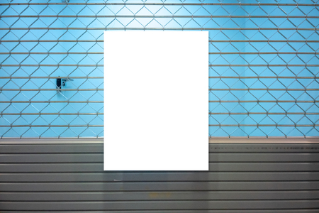 White paper notification on rolling metal door with blue wall behind.