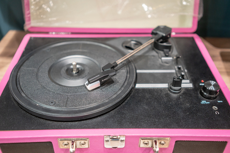 Pink and black modern vinyl player on wooden table. Retro vintage style.