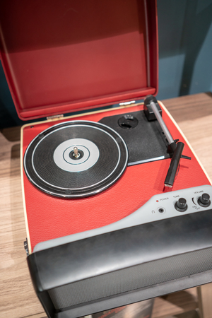 Red and black modern vinyl player on wooden table. Retro vintage style. Stockfoto