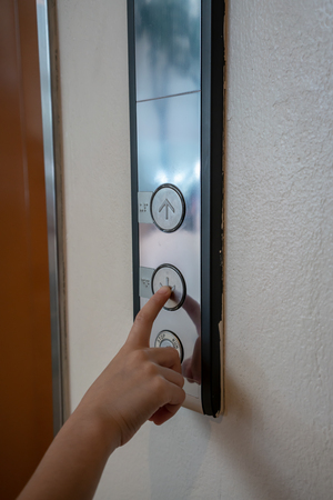 A finger reaches for pressing the button of the elevator or lift in office building.