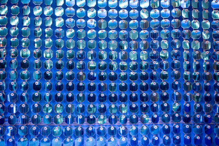 Glittering shiny blue sequin wall decoration for texture and background. Closed up view from lower angle.