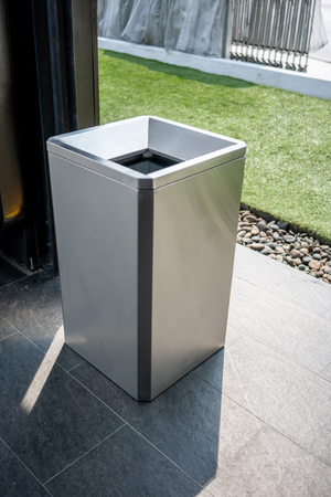 Stainless modern silver square shape trash bin on dark outdoor floor 免版税图像