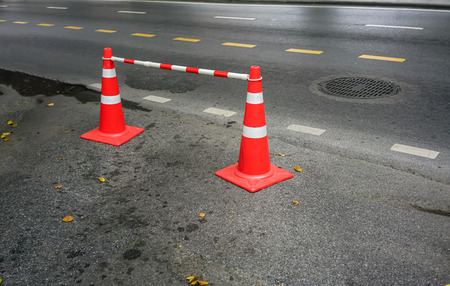 Two orange traffic cones on concrete road standing to close some part of road.