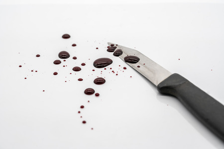 Closed up bloody kitchen knife with blood spatter and droplet on white background for Haloween concept.