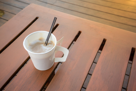 Single hot latte on plank wood table at relaxing balcony from high angle. Paper coffee cup. 版權商用圖片