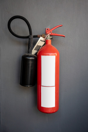 Red fire extinguisher hanging against dark grey wall background Stock Photo