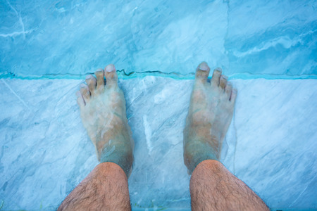 Feet in the water at the swimming pool. Relaxing or sporting concept.