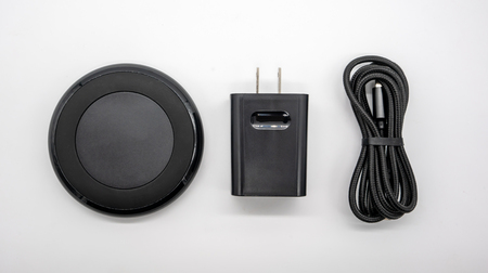 Black round shape wireless charger and adapter isolated on white background. Stockfoto