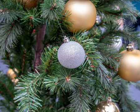 Hanging shiny silver and golden balls and silver Christmas wreath with tinsel and ornaments for seasonal greeting.