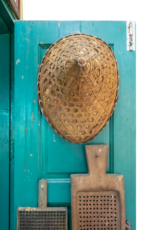 Traditional hat made of bamboo wood and dry leaves hanging on blue green door background.