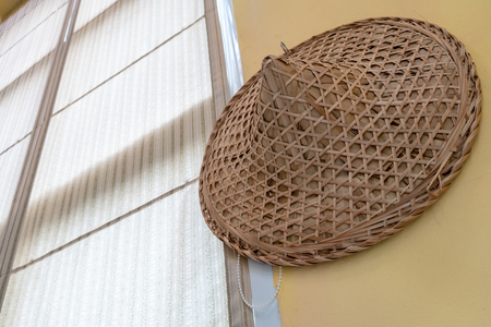 Traditional hat made of bamboo wood and dry leaves hanging on yellow wall background.