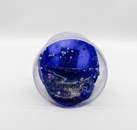 Dark transparent blue glitter slime in clear plastic container isolated on white background