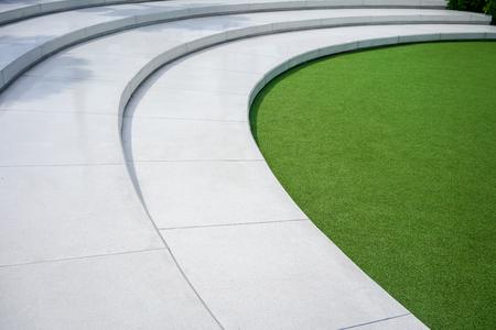 Herbe verte artificielle avec des escaliers en béton blanc pour le concept de décoration sur le thème de la nature. Amphithéâtre extérieur. Banque d'images