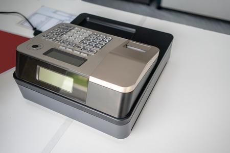 Silver cash register on white counter. Portable model cashing machine on white. Imagens