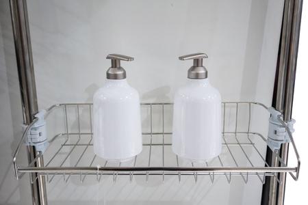Two white dispenser bottles on metal bathroom shelf. Stock Photo
