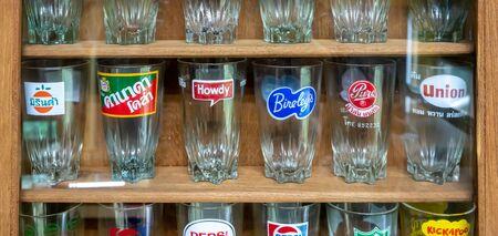Bangkok, Thailand - Sept 24, 2018 : Old premium popular sodabeverage brand glasses in wooden display shelf.