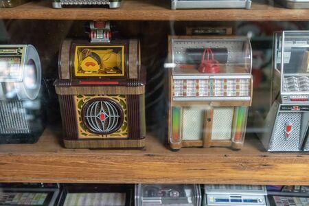 Bangkok, Thailand - Sept 24, 2018 : Mini vintage retro jukebox music machine in wooden shelf display. Editorial
