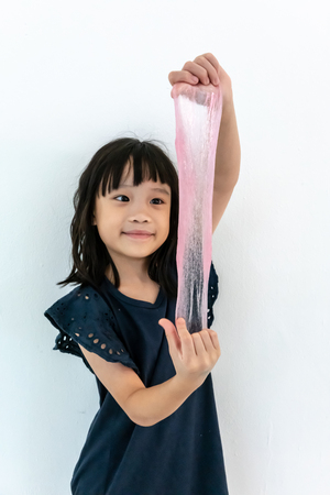 Funny Asian girl playing with pink slime. Childhood, leisure and people concept