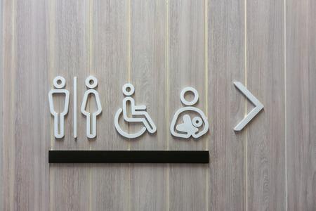 Segno moderno del bagno maschio, femmina, disabilità e bambino con direzione a destra su sfondo di legno