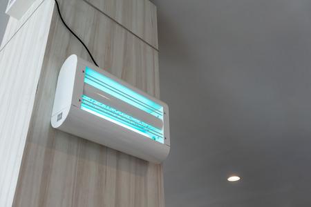 Tueur électrique de mouches et d'insectes avec lampe UV bleue et verte sur fond de mur en bois. Protège de manière fiable contre les insectes.
