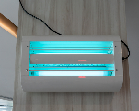 Electric fly and insect killer with blue and green UV lamp on wooden wall background. Reliably protects from insects.