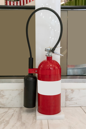 Fire protection equipment, Fire extinguisher on white stand located near escalator