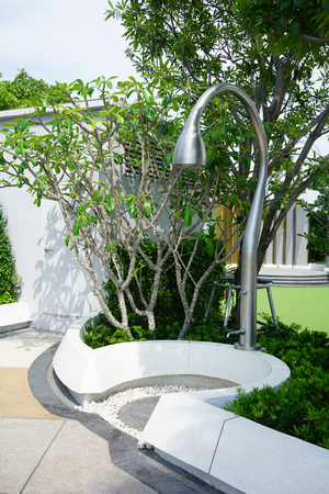 Modern outdoor shower area surrounded by planting within swimming pool area. Landscape detail design. Фото со стока
