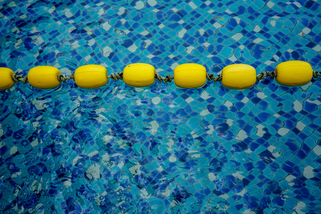 Yellow lanes in blue pool water close-up. Blue pool water and yellow swimming lane marker in swimming pool Imagens