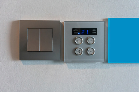 Grey metallic light switch and air condition controller with digital display against white wall background.